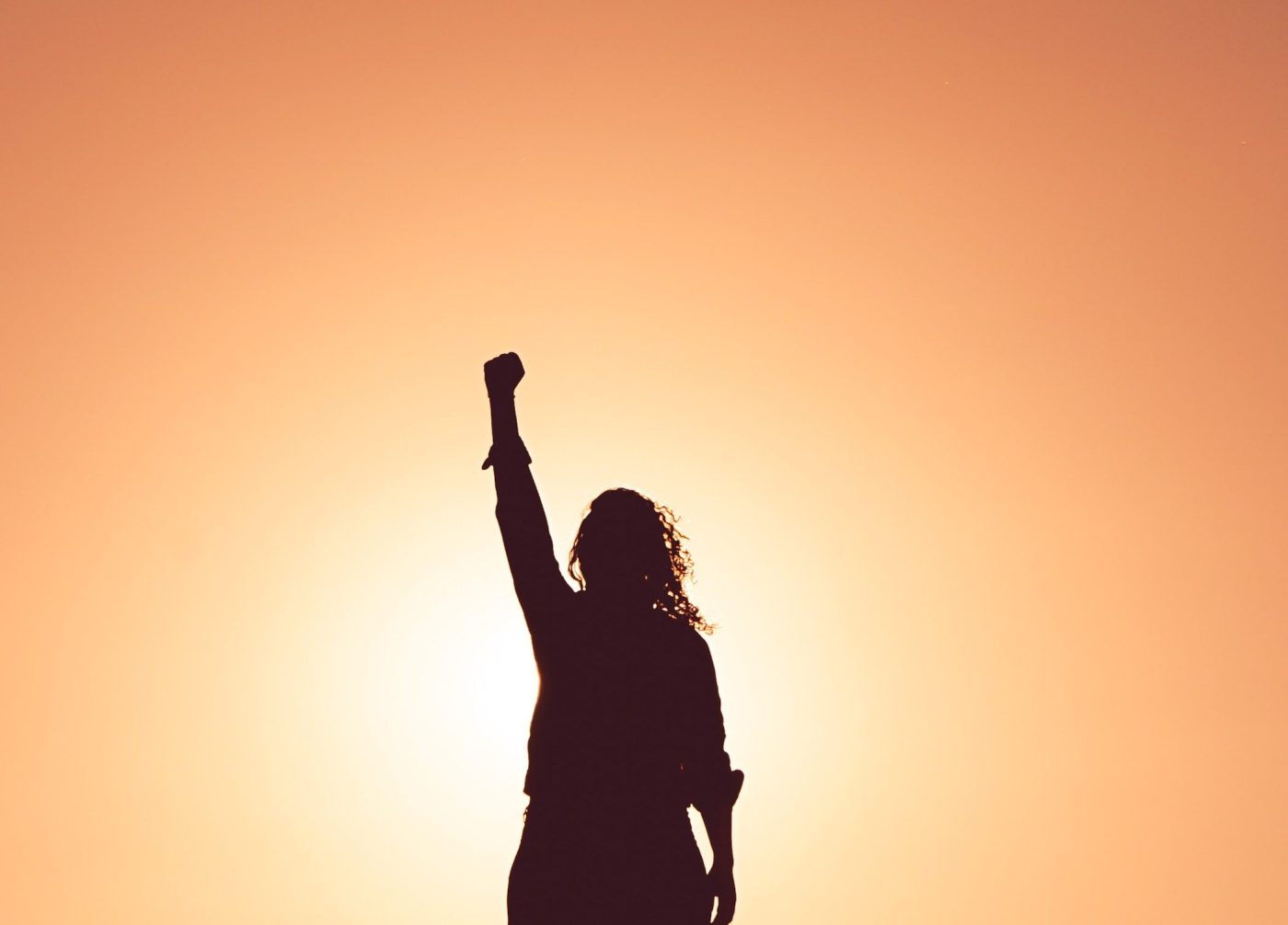silhouette of determined employee standing triumphantly with arm raised and the sun at their back having learned self determination from situational leadership instruction Photo by Miguel Bruna on Unsplash