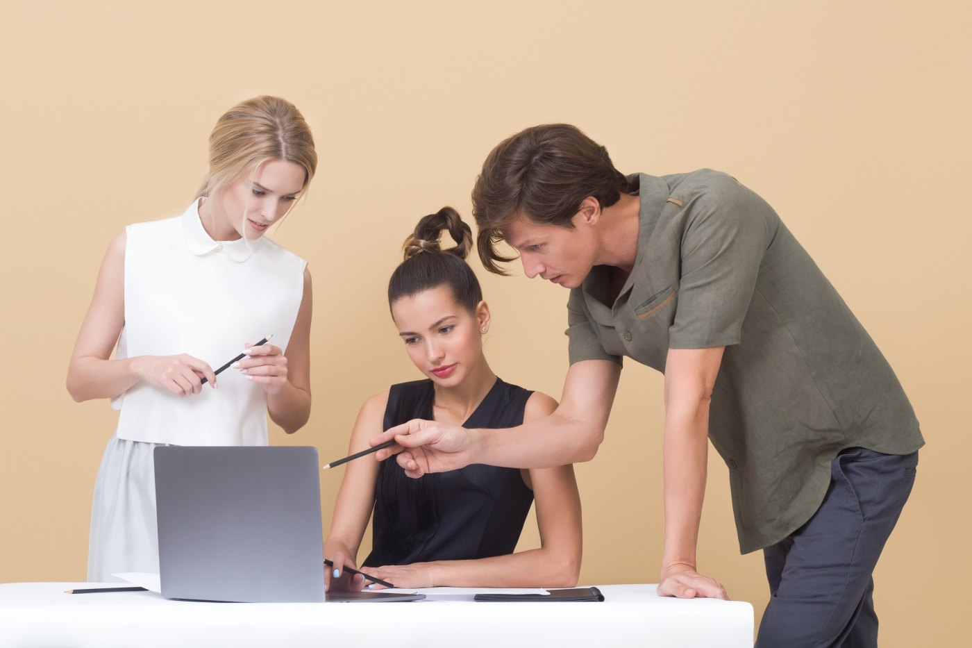 three employees looking at one laptop with one being the clear leader discussing their future leadership roles with the organization Photo by Icons8 team on Unsplash
