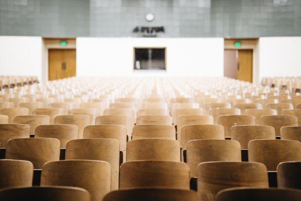 empty chairs in college auditorium style business ethics class discussing the Effectiveness of Professional Ethics Education studies can be to the student. Photo by Nathan Dumlao on Unsplash