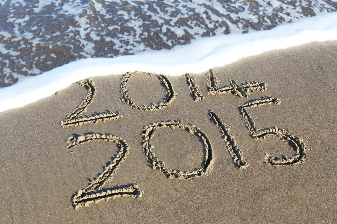 ocean wave washing away part of the years 2014 and 2015 that are written in sand representing a positive office culture for the new year ahead