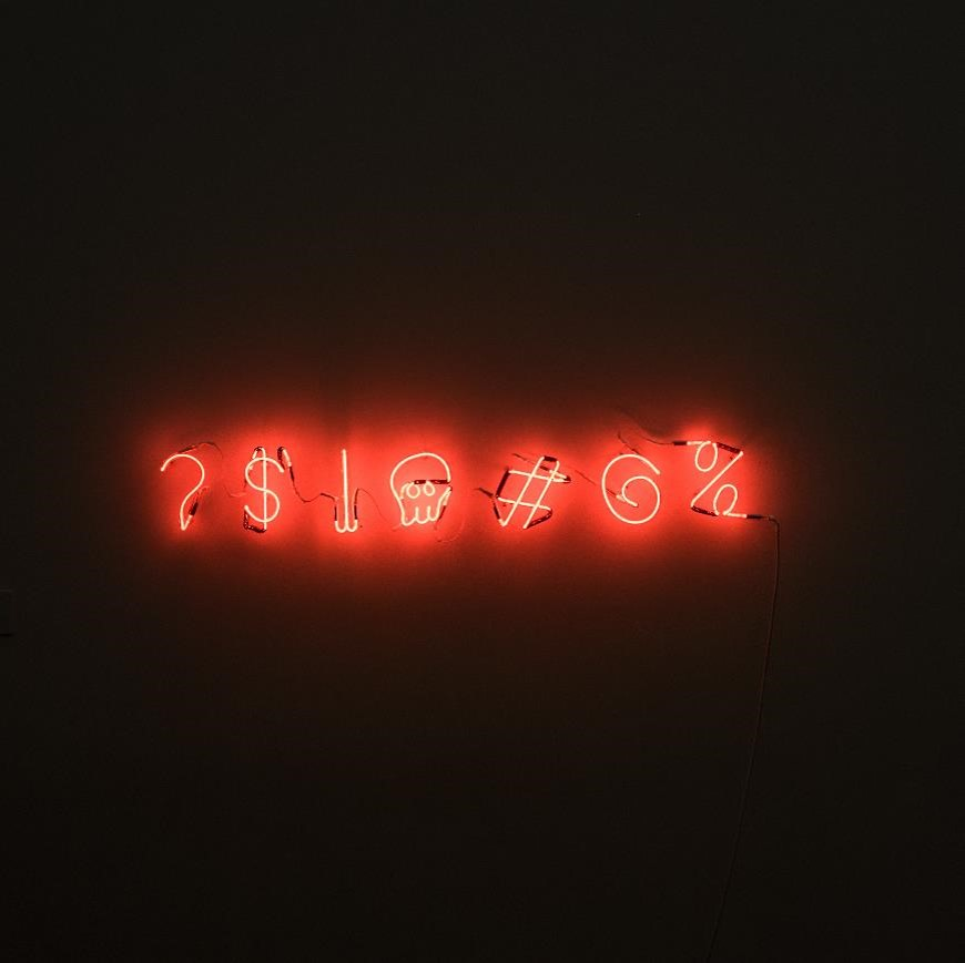 red neon sign of various punctuation and symbols on dark, black wall representing the challenges of managing emotions in tough decisions