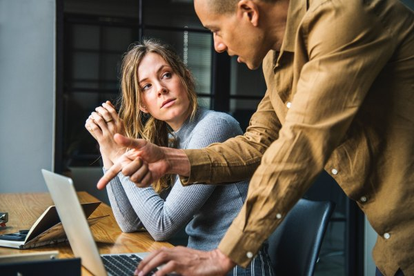 office manager pointing to a laptop screen talking with an employee who is looking at him with a serious face recognizing the importance of training managers to be mediators