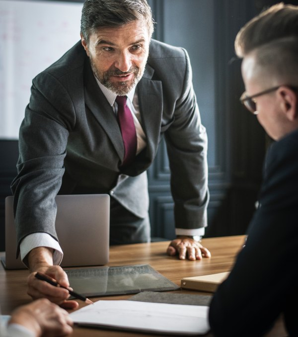 Male authoritative figure pointing at document with a pencil making eye contact with subordinate showing Authentic Leadership by Earning Trust and Respect