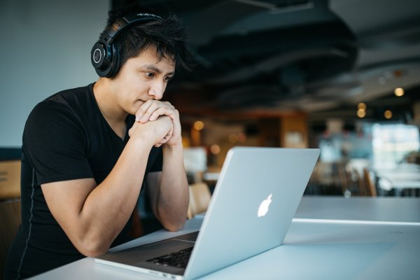 man with headphones looking intently at laptop considering Online Dispute Resolution Methods for Employee Conflict he is experiencing