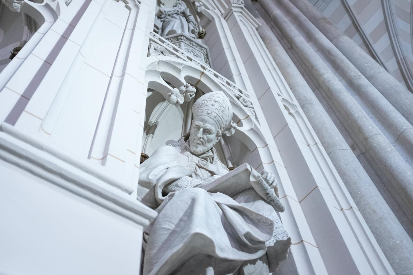 Marble statue carved out of a building of priest staring down upon the onlooker
