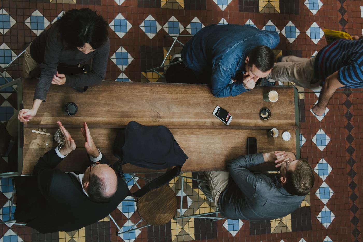 Overhead view of 4 people having discussions at a table in Arbitration