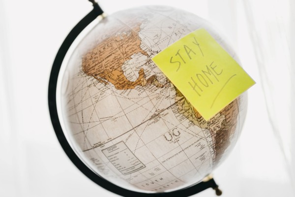 "Globe with ""stay home"" post-it representing the global pandemic and quarantine mandates"