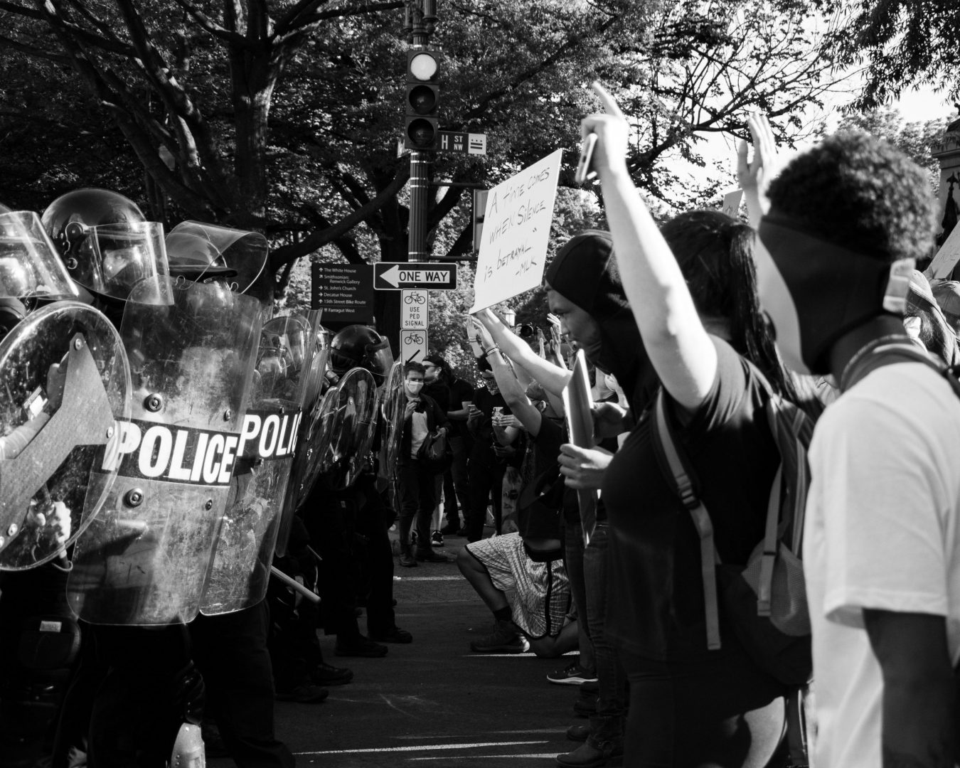 Black and white image of police in riot gear facing protestors on city street